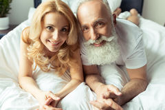 Happy mature couple in love lying together in bed and smiling at camera Royalty Free Stock Photography