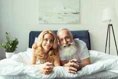 Happy mature couple in love lying together in bed and smiling at camera Stock Images