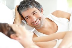 Happy mature couple lying on bed smiling Stock Photography