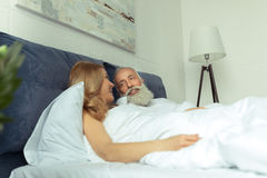 Happy mature couple lying together in bed and smiling each other Stock Photo