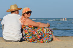 Happy mature couple man & woman sitting at seashore on sandy beach Royalty Free Stock Photo