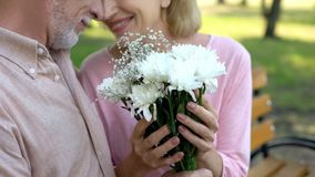 Happy mature couple nuzzling, holding white flowers bouquet, sitting park bench royalty free stock images