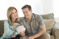 Happy Mature Couple With Piggybank At Home Stock Photo