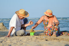 Happy mature couple playing at seashore on sandy beach. Mature couple playing like kids at seashore on sandy beach back to back Stock Image