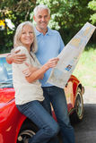 Happy mature couple reading map together Stock Image