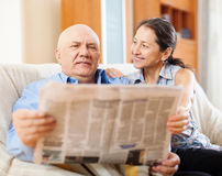 Happy mature couple reading newspaper Stock Image