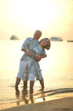 Happy Mature couple. Relaxing on beach at sunset Royalty Free Stock Photos