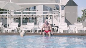 Happy mature couple relaxing at the pool in the hotel complex together. Cute senior man sitting on the edge of pool stock video