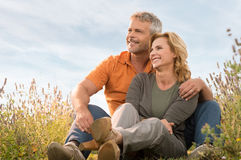 Happy Mature Couple Relaxing. Portrait Of A Happy Mature Couple Sitting In Field And Contemplate The Future Royalty Free Stock Images