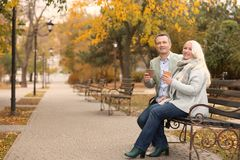 Happy mature couple resting on bench stock photo