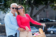 Happy mature couple riding bicycle in city Stock Photo
