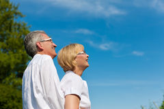 Happy mature couple or senior looking to the blue. Happy mature couple - senior people (men and women) already retired - looking to the blue sky in summer stock photo