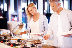 Happy mature couple serving food at buffet Royalty Free Stock Image