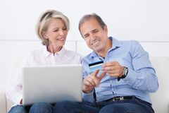 Happy mature couple shopping on laptop Stock Photography