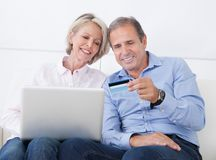Happy mature couple shopping on laptop Stock Images