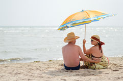 Happy mature couple sitting at seashore on sandy beach. Back to back Royalty Free Stock Photos