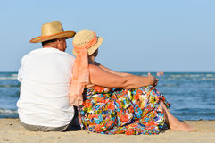 Happy mature couple sitting at seashore on sandy beach. Mature couple sitting at seashore on sandy beach back to back on sea summer outdoors background Stock Photography