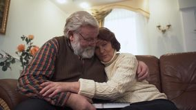 Happy mature couple sitting on the sofa in modern living room at home. Elder man and woman cuddle each other. Leisure of. Happy mature couple sitting on the sofa stock footage