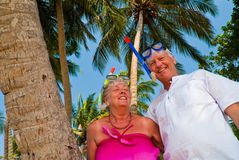 Happy mature couple with snorkeling gear. Happy mature couple smiling in the shade of palm trees on the beach. They are wearing snorkeling gear and in the Stock Image