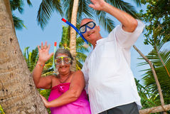 Happy mature couple with snorkeling gear waving. Happy mature couple smiling and waving in the shade of palm trees on the beach. They are wearing snorkeling gear Royalty Free Stock Photos