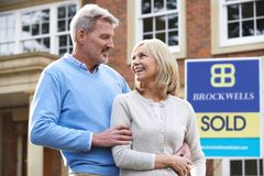 Happy Mature Couple Standing Outside House With Sold Sign royalty free stock images