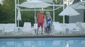 Happy mature couple standing at the swimming pool hugging their little granddaughter. Grandmother and grandfather. A happy mature couple standing at the swimming stock video