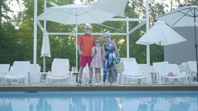 Portrait happy mature couple standing at the swimming pool hugging their little granddaughter. Grandmother and. A happy mature couple standing at the swimming stock footage
