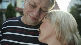 Happy mature couple standing in from of their home and looking at camera. stock footage