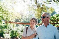 Happy mature couple standing together in a park Stock Photography
