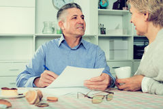 Happy mature couple at table attentively study documents. And sign agreement stock photo