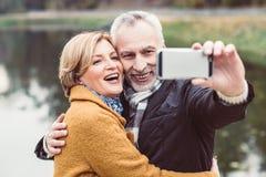 Happy mature couple taking selfie stock photos