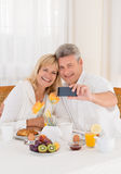 Happy mature couple taking a selfie photo on their mobile phone while having healthy breakfast. Happy couple seated at the breakfast table spread with healthy Stock Photo