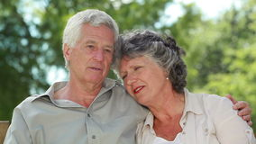 Happy mature couple talking while sitting on a wooden bench Stock Photo