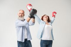 Couple triumphing in boxing gloves. Happy mature couple triumphing in boxing gloves, isolated on white Royalty Free Stock Photo