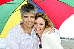 Happy mature couple with umbrella Royalty Free Stock Photos