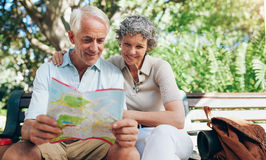Happy mature couple using city map for direction stock photography