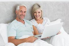 Happy mature couple using laptop in bed Stock Image