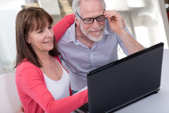 Happy mature couple using laptop Royalty Free Stock Images