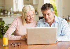 Happy mature couple using laptop Stock Image