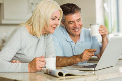 Happy mature couple using laptop Stock Photography
