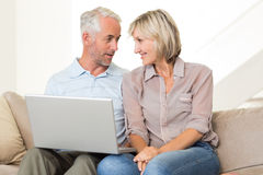 Happy mature couple using laptop on sofa Stock Photos
