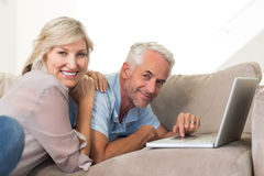 Happy mature couple using laptop on sofa Stock Photography