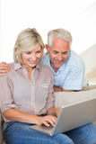 Happy mature couple using laptop on sofa Royalty Free Stock Photo