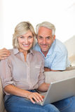 Happy mature couple using laptop on sofa Stock Photo