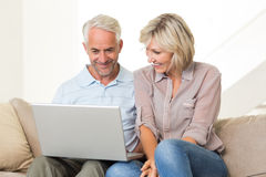 Happy mature couple using laptop on sofa Royalty Free Stock Photography