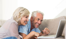 Happy mature couple using laptop on sofa. Side view of a happy mature couple using laptop on sofa at home Stock Photo