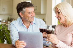 Happy mature couple using tablet drinking red wine stock photos