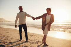 Happy mature couple walking along the beach Royalty Free Stock Photography