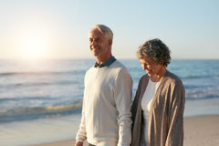 Happy mature couple walking along the beach Royalty Free Stock Image