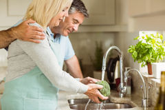 Happy mature couple washing broccoli Royalty Free Stock Photos